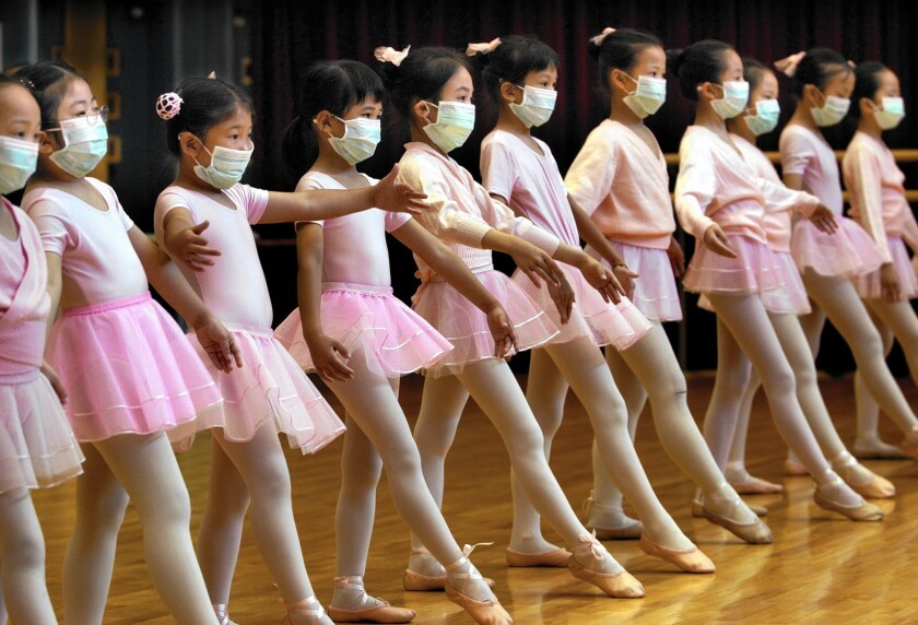 Young ballet students in Hong Kong wear protective masks in April 2003, during the height of the SARS scare in the city.