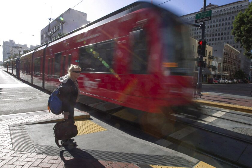 A pedestrian waited on C street as the trolley passed her in May.