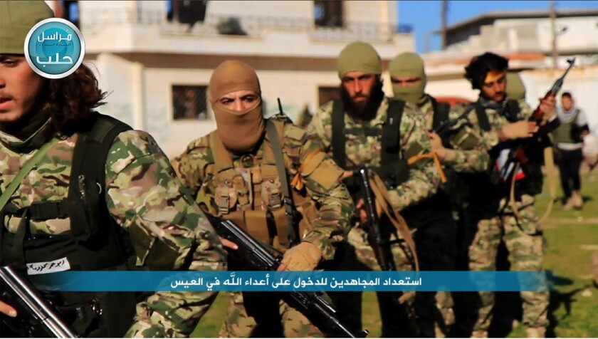 This file photo posted on the Twitter page of Syria's Nusra Front on April 1 shows Nusra Front fighters marching toward the northern village of al-Ais in Aleppo province, Syria.