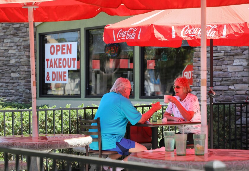 Larry and Connie Clay eat under the red umbrellas at one of the outdoor dining areas at J&M Family Restaurant.