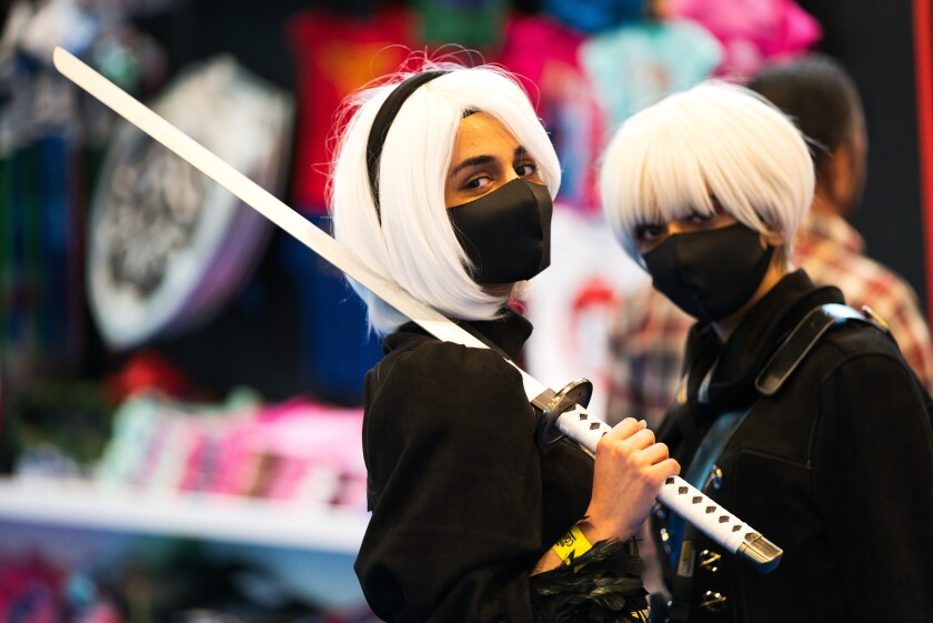 Two women wearing masks dressed as sword-wielding anime characters pose for a photograph at the Middle East Film & Comic Con in Dubai, United Arab Emirates, Thursday, March 5, 2020. The Middle East Film & Comic Con began Thursday night in Dubai, a city of skyscrapers and nightclubs suddenly subdued by the outbreak of the new coronavirus across the region. (AP Photo/Jon Gambrell)