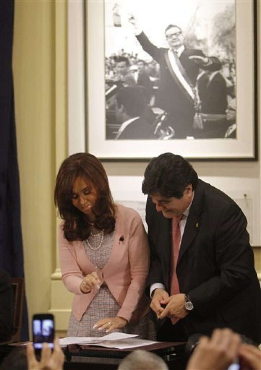 Argentina's President Cristina Fernandez, left, gestures after signing the same sex marriage bill at the Latin America Patriots room of the government house in Buenos Aires, Wednesday, July 21, 2010. At right, Carlos Zanini, Argentina's Presidency legal aid and atop a photo of Chile's late Presiden