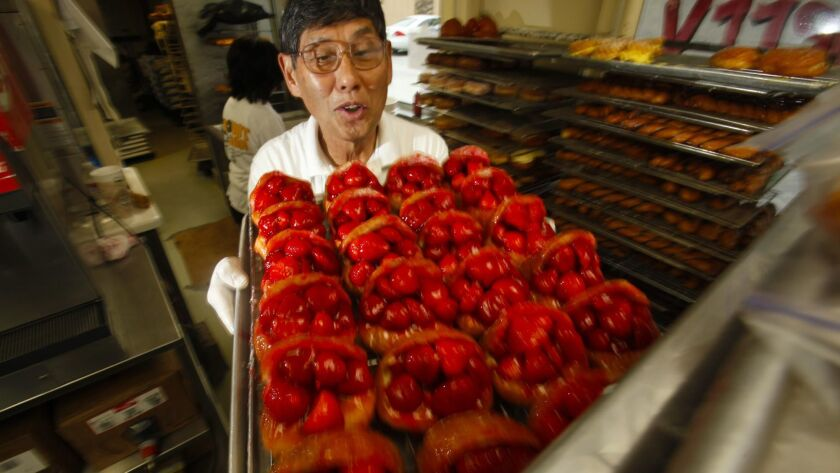 The Donut Man founder Jim Nakano with a tray of his strawberry donuts in 2011. The beloved shop will expand to downtown L.A.'s Grand Central Market next year.