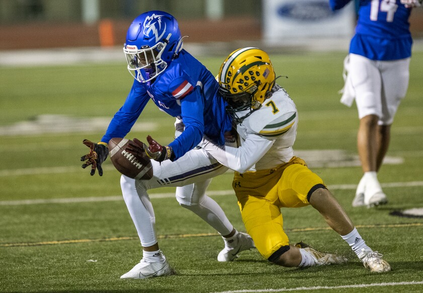 Edison's Logan Gregory knocks the ball loose from Los Alamitos' Ethan O'Connor during a Sunset League game on Thursday.
