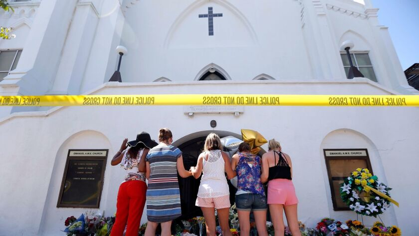 A group of women pray together at a makeshift memorial in front of the Emanuel AME Church, in Charleston, S.C. on June 18, 2015.