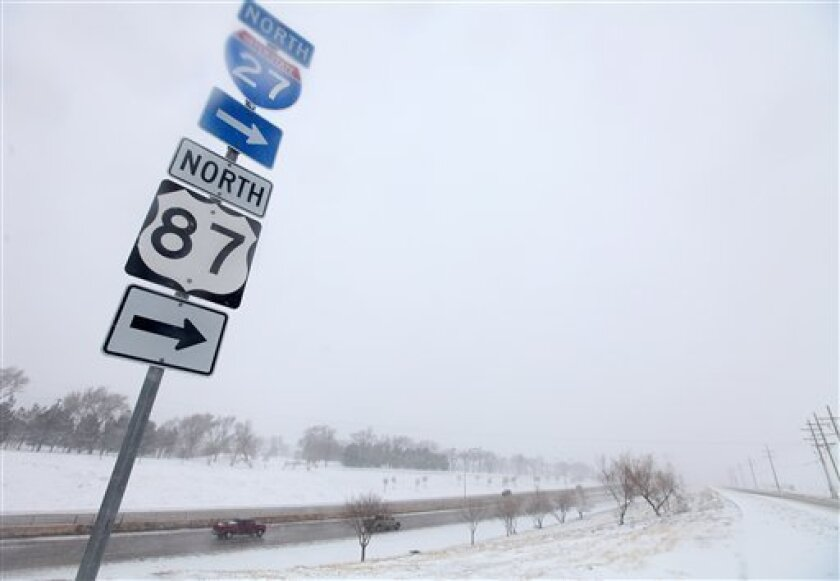 Vehicles navigate along Interstate 27 during blizzard conditions in Lubbock, Texas, Monday, Feb. 25, 2013. State troopers are unable to respond to calls for assistance and National Guard units are mobilizing as a winter storm blankets the central Plains with a foot of snow in some places. Roads are closed Monday throughout West Texas and the Panhandle. (AP Photo/Lubbock Avalanche-Journal, Zach Long)