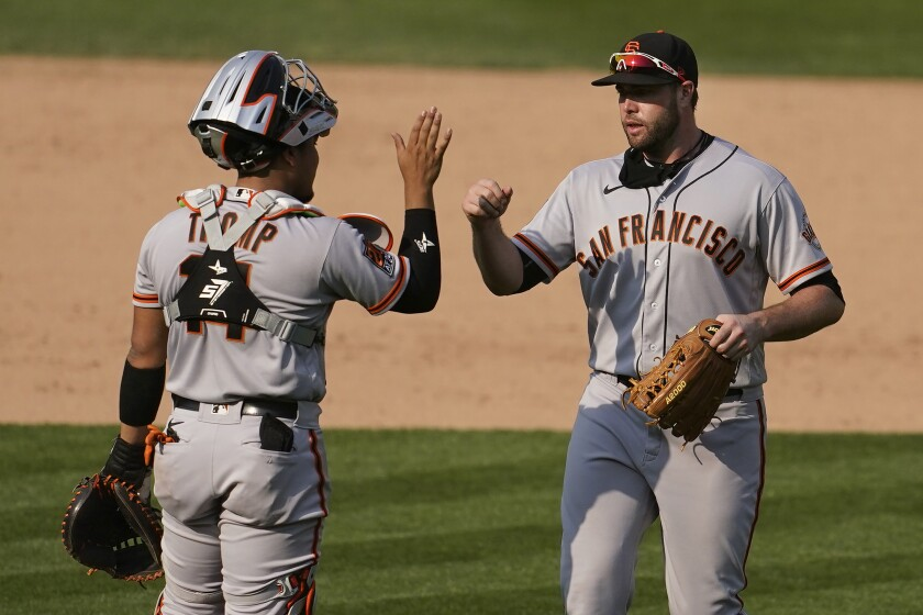 San Francisco Giants catcher Chadwick Tromp, left, celebrates with Darin Ruf after they defeated the Oakland Athletics in a baseball game in Oakland, Calif., Sunday, Sept. 20, 2020. (AP Photo/Jeff Chiu)