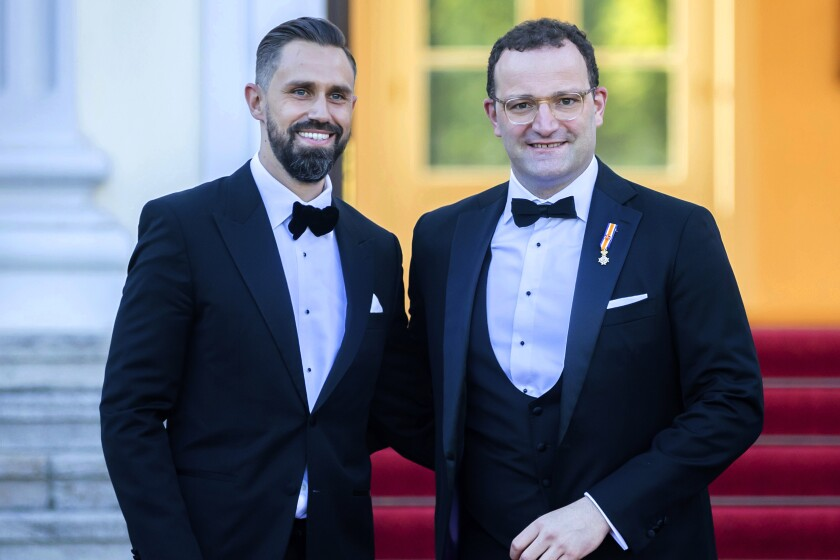 FILE-In this July 5, 2021 taken photo shows German Health Minister Jens Spahn, right, and his husband Daniel Funke, left, arriving at Bellevue presidential palace to attend a State banquet hosted by the Federal President and his wife in Berlin. Germany's health minister, who has been an ever-present appearance in the country's media and public since the outbreak of the coronavirus pandemic, has criticized the Catholic Church for its refusal to bless same-sex couples. (AP Photo/Christoph Soeder)