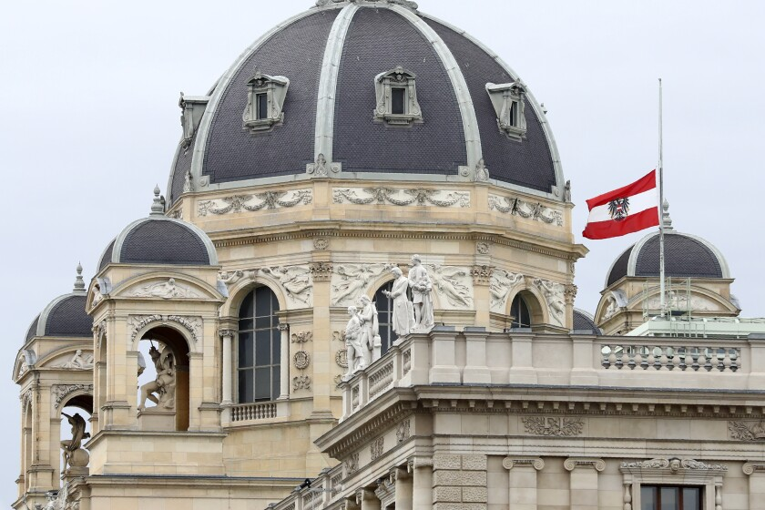 The Austrian national flag waves of half-mast on a building downtown in Vienna, Austria, Wednesday, Nov. 4, 2020. Several shots were fired shortly after 8 p.m. local time on Monday, Nov. 2, in a lively street in the city center of Vienna. (AP Photo/Matthias Schrader)