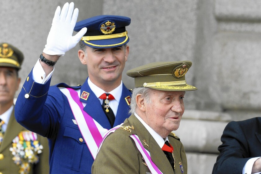 King Juan Carlos, right, and Crown Prince Felipe take part in a military event in Madrid in January. Juan Carlos announced his intention to abdicate and pass the crown to his son.