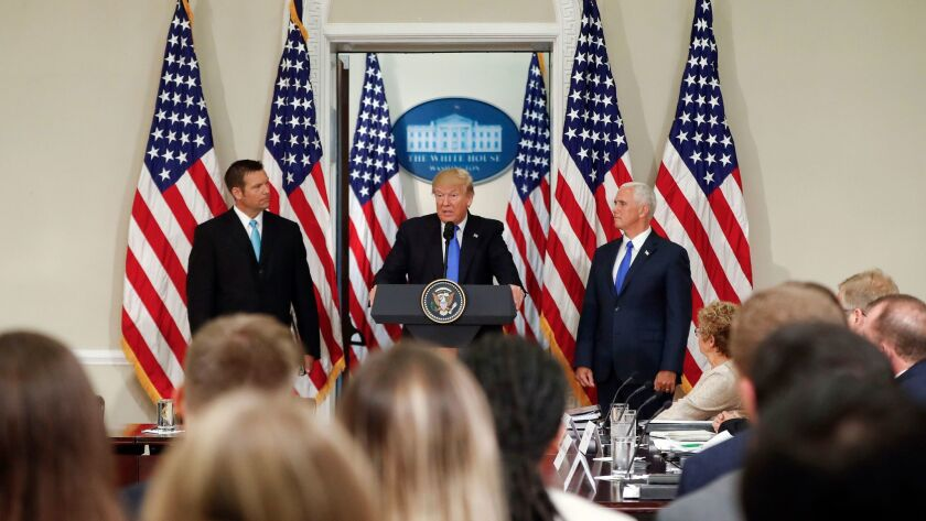 President Trump, with Kansas Secretary of State Kris Kobach, left, and Vice President Mike Pence, speaks at a meeting of the Presidential Advisory Commission on Election Integrity on July 19 in Washington.