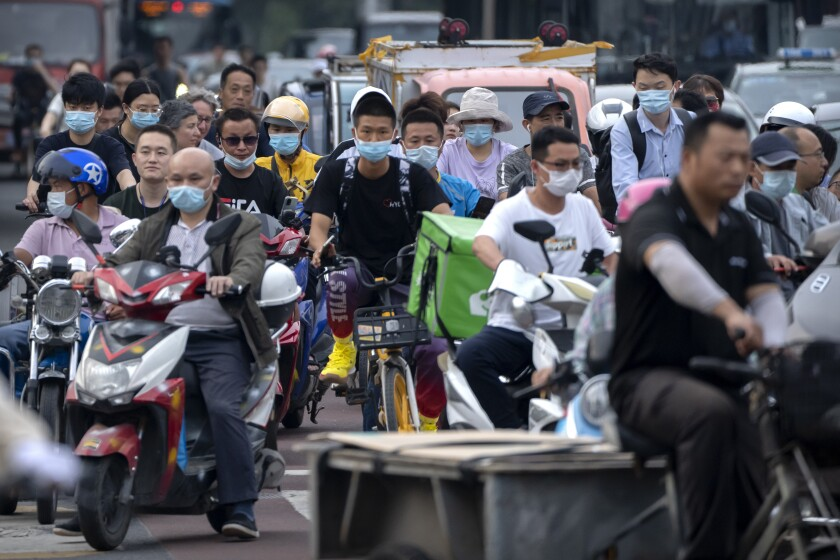 People riding bicycles and scooters wait to cross an intersection during rush hour in Beijing.