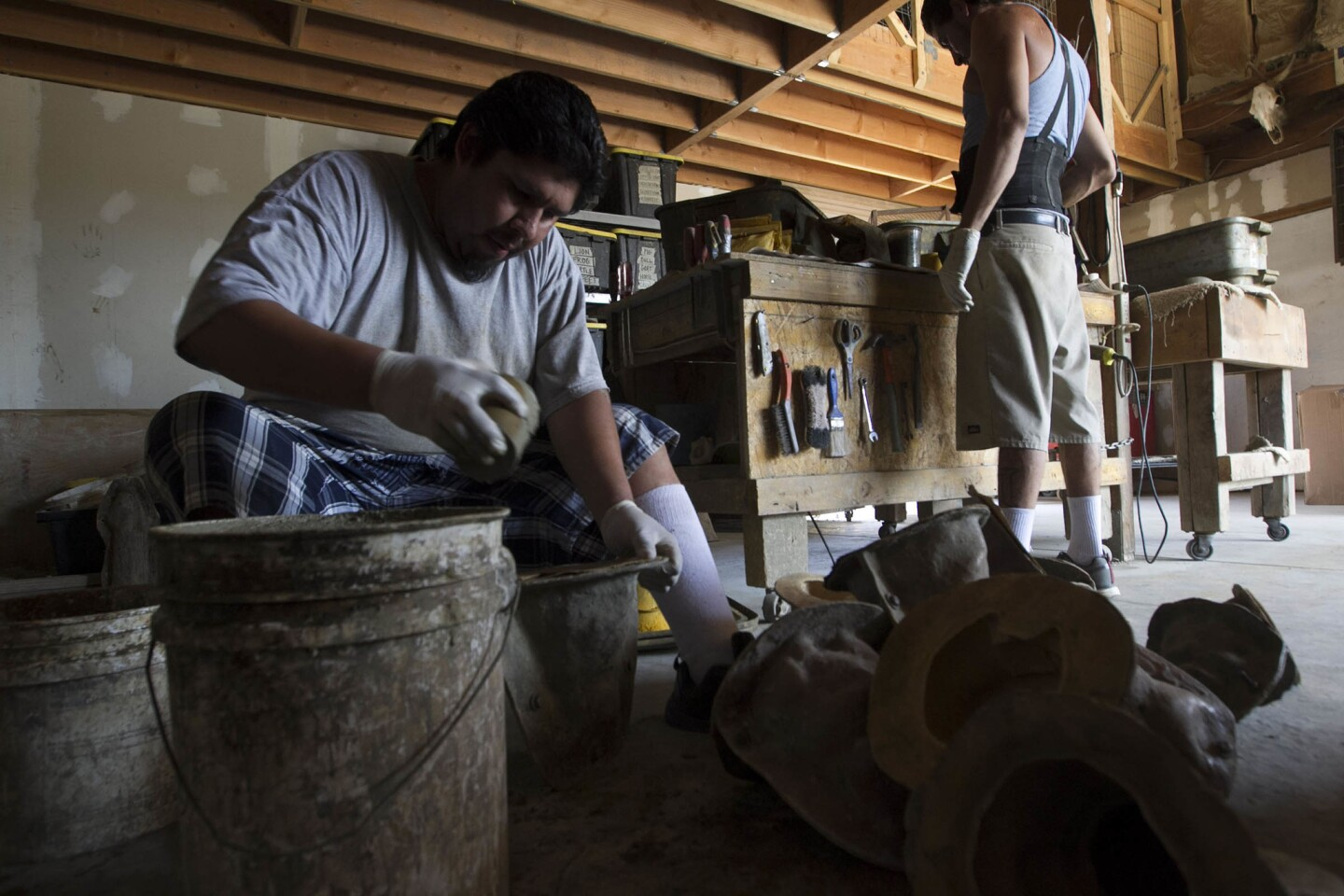 Eduardo Morales, left, shook a mold filled with a cement mixture in to a piece of garden statuary at the Designer Stone Garden Shop in Ramona.