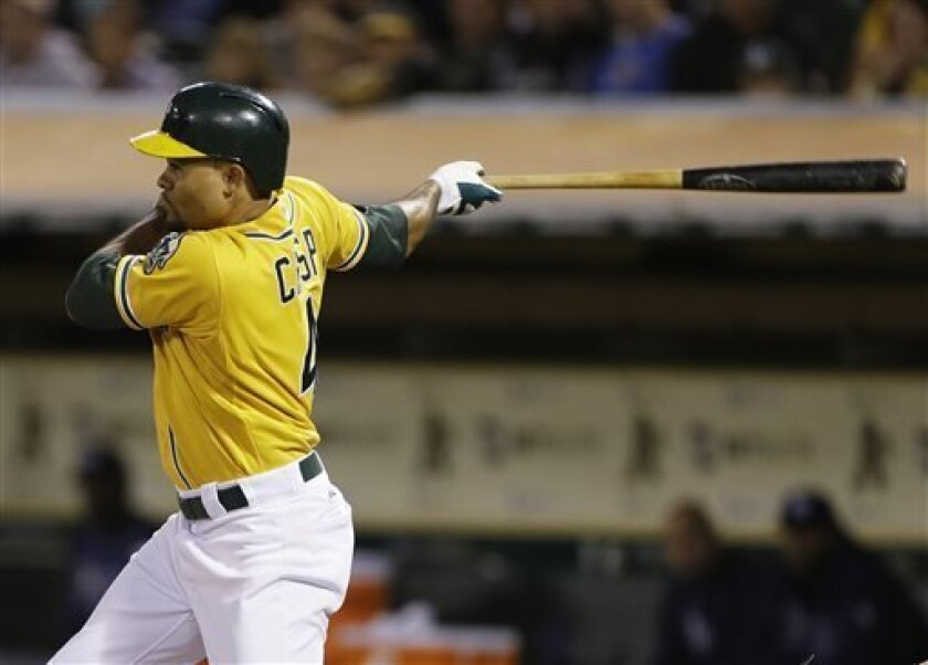 Oakland Athletics' Coco Crisp hits an RBI single off Tampa Bay Rays starting pitcher Alex Cobb during the sixth inning of their baseball game Saturday, Aug. 31, 2013, in Oakland, Calif. (AP Photo/Eric Risberg)