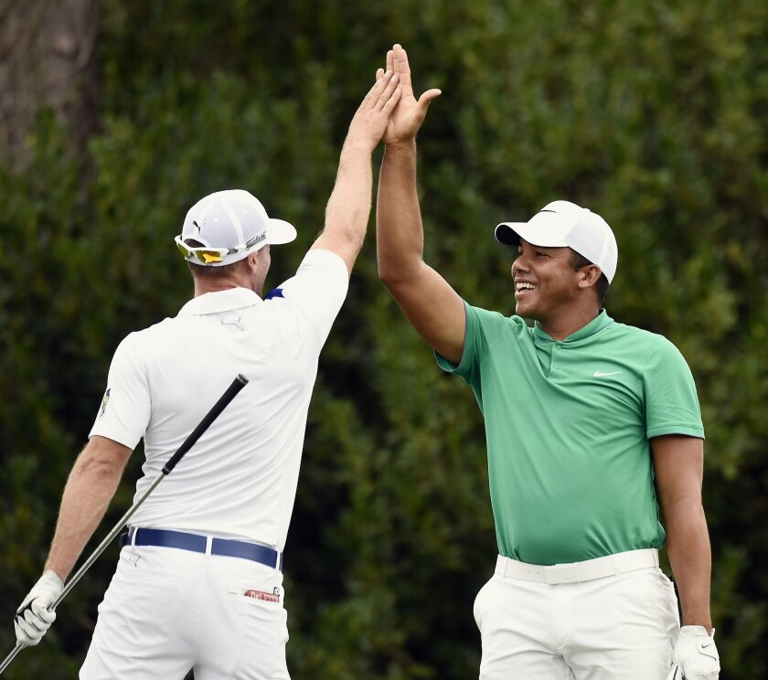 Jhonattan Vegas, right, of Venezuela, celebrates with Graham DeLaet, of Canada, after Vegas hits a hole-in-one on the 17th hole during second round play at the Barbasol Championship golf tournament Friday, July 15, 2016, in Opelika, Ala. (Dakota Sumpter/Opelika-Auburn News via AP)