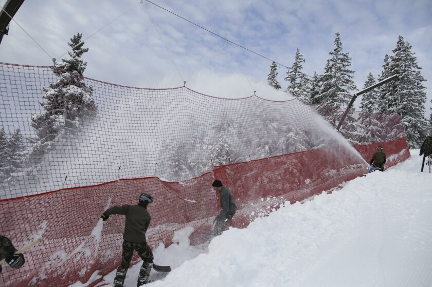 Soldiers shovel snow after an alpine ski, women's World Cup downhill race was canceled, following a heavy snowfall, in Crans Montana, Switzerland, Saturday, Feb. 13, 20176. (AP Photo/Alessandro Trovati)