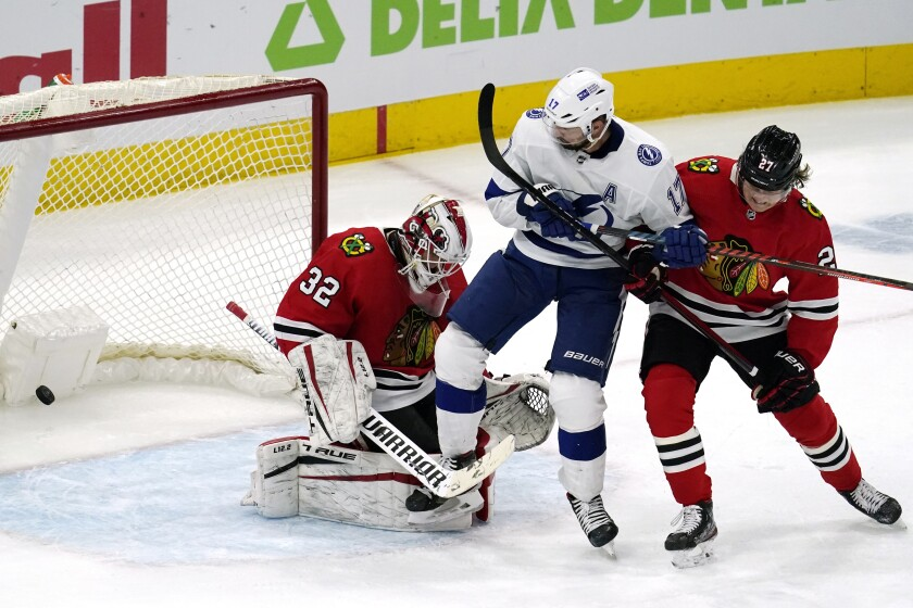 RETRANMISSION TO CORRECT THAT ALEX KILLORN SCORED - Chicago Blackhawks goalie Kevin Lankinen, left, cannot make the save on the game-winning goal by Tampa Bay Lightning's Alex Killorn (17) as Chicago Blackhawks' Adam Boqvist defends during overtime period of an NHL hockey game in Chicago, Thursday, March 4, 2021. The Lightning won 3-2 in overtime.(AP Photo/Nam Y. Huh)