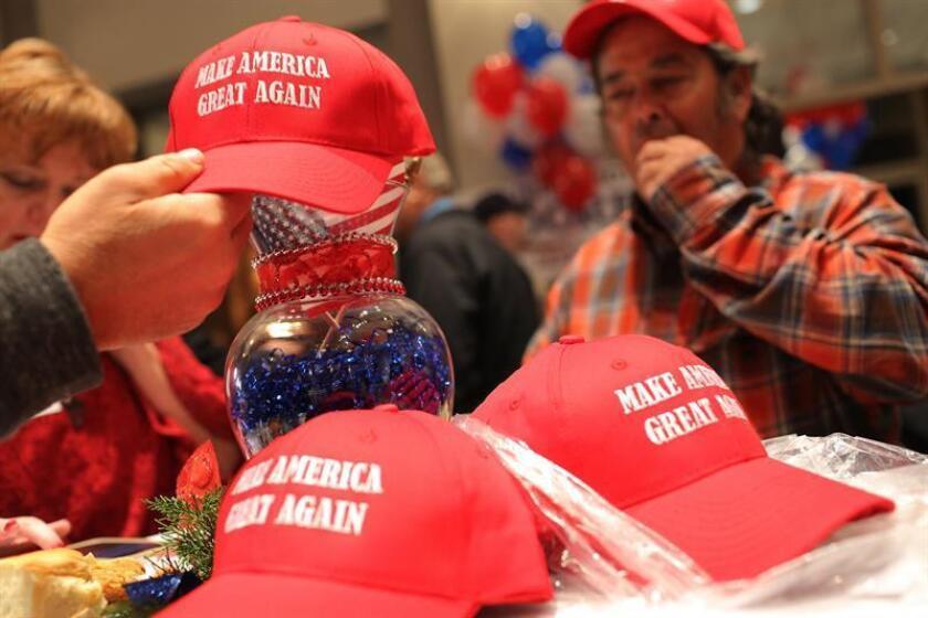 Partidarios de Roy Moore posan sobre el estrado con el lema de campaña del presidente estadounidense Donald J. Trump en la fiesta de vigilancia del candidato republicano al Senado Roy Moore en Montgomery, Alabama, EE. UU. hoy, 12 de diciembre de 2017. EFE
