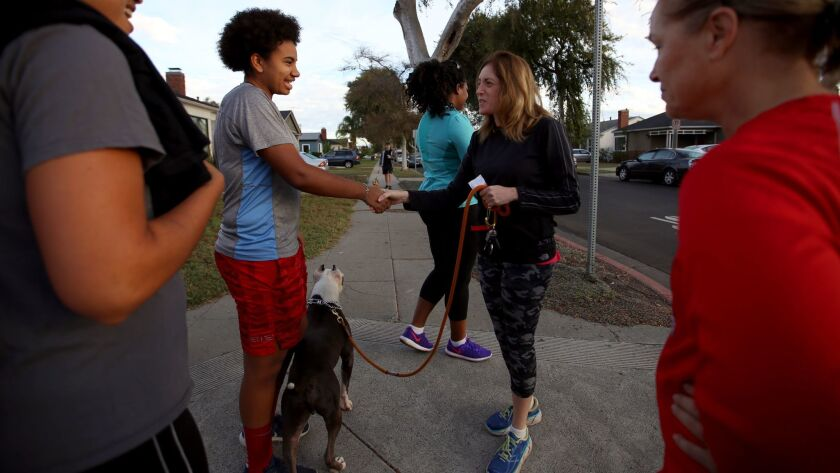 Moreau Halliburton, left, greets Robyn Stern before a group walk in Leimert Park.