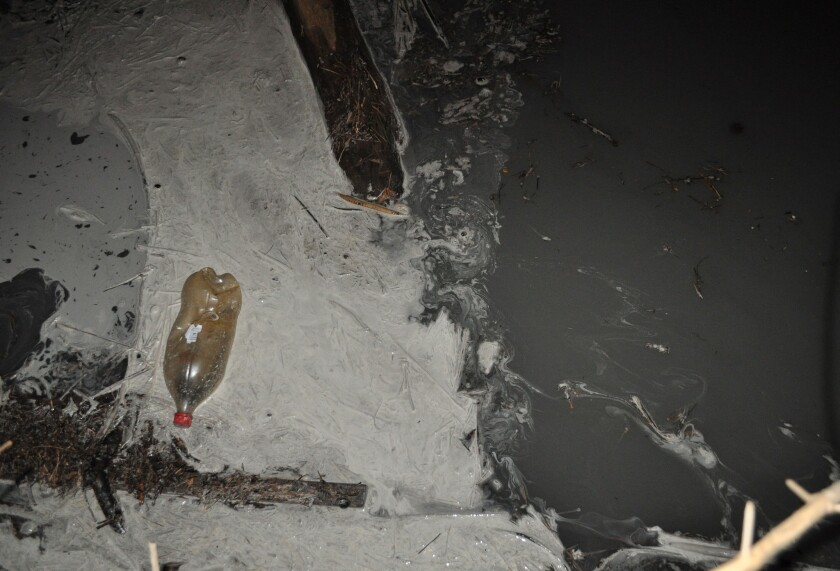 What might be coal ash is seen in a Monday photo of the Dan River in Eden, N.C. Duke Energy says tens of thousands of tons of coal ash spilled into the river Sunday.