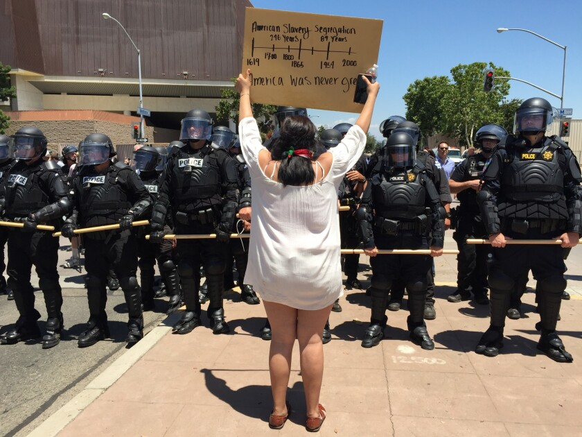 A skirmish line of 50 or so Fresno police officers, clad in black riot gear, slowly move protesters out of the street.