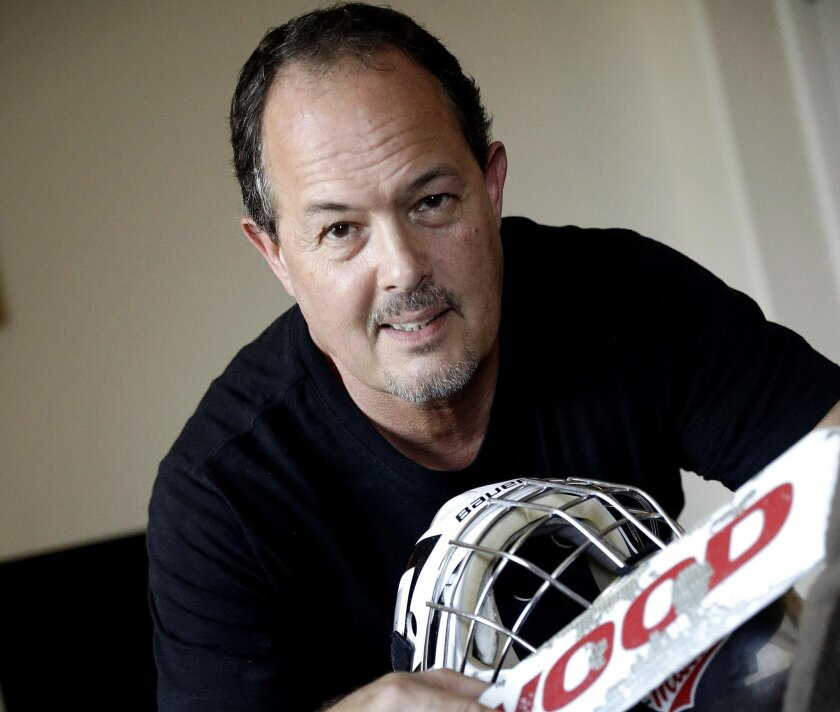 In this Thursday, July 28, 2016, photo, Tim Richmeier poses for a photo with some of his 15-year-old son's hockey equipment, in Phoenix. Richmeier was spending about $5,000 a season using his tax refunds, halting contributions to his 401(k), and putting travel expenses on a credit card, including $