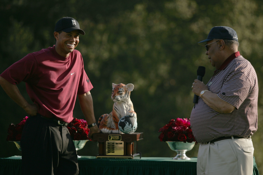 Tiger Woods laughs as his father Earl Woods presents him with a trophy.