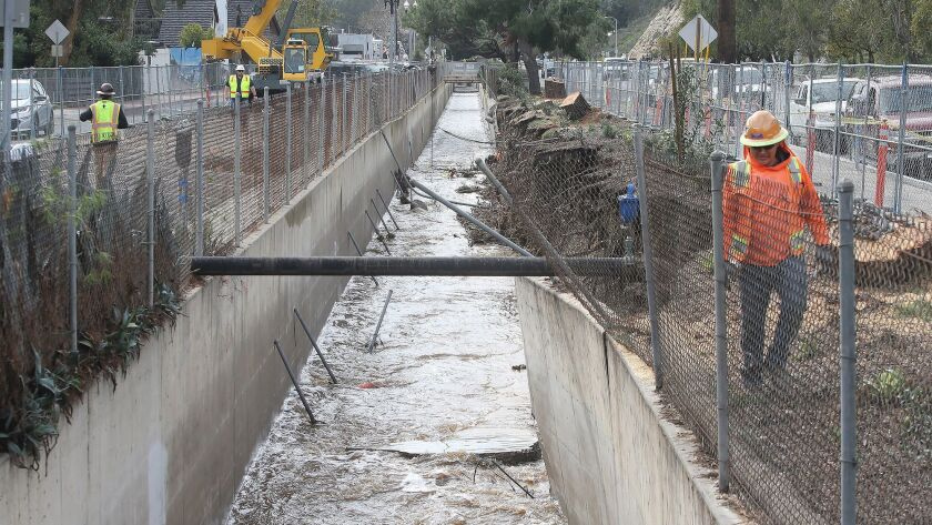 A member of the OC Public Works team looks for damage along a storm drain heavily damaged in Laguna