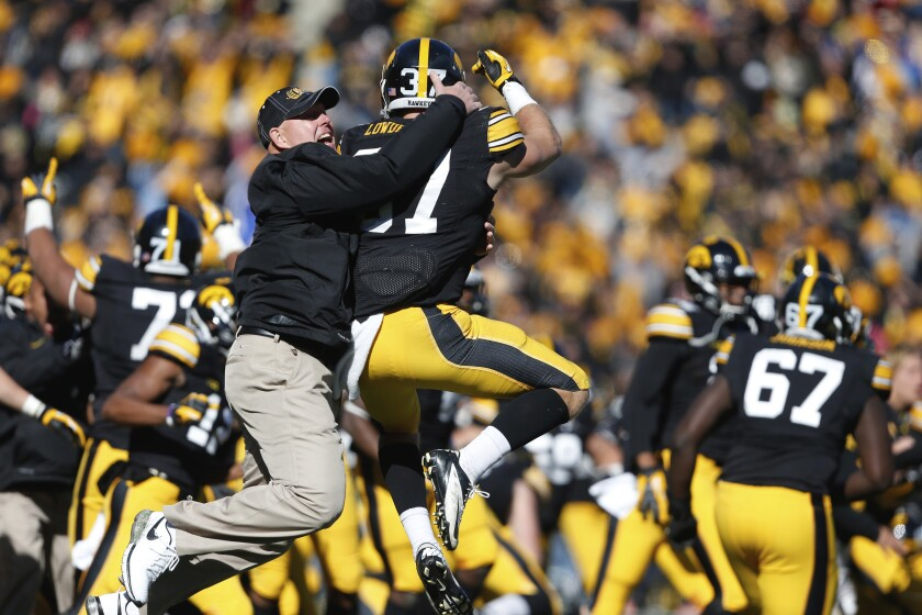 "FILE - In this Oct. 26, 2013, file photo, Iowa strength and conditioning coach Chris Doyle, front left, celebrates with defensive back John Lowdermilk (37) following their win in overtime against Northwestern in an NCAA college football game in Iowa City, Iowa. Iowa football strength and conditioning coach Doyle has been placed on administrative leave after several black former players posted on social media about what they described as systemic racism in the program. Head coach Kirk Ferentz made the announcement Saturday, June 6, 2020, calling it ""a defining moment"" for Iowa's football program in a video posted on the team's Twitter account. (AP Photo/Brian Ray, File )"
