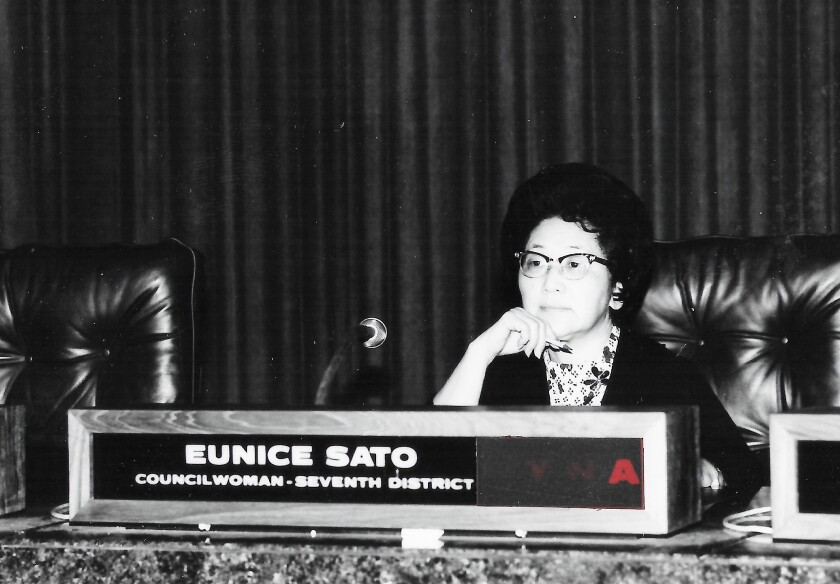 Eunice Sato sits at her desk.
