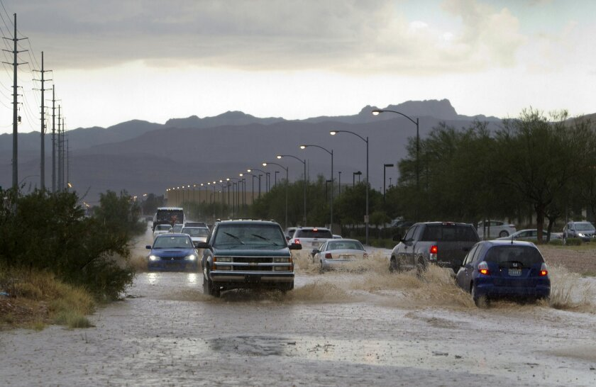 Cars and trucks drive through run-off on Sunset Road near Jones Boulevard after a thunderstorm dropped heavy rain and hail in the Las Vegas valley Thursday, June 30, 2016. The National Weather Service issued a flash flood warning after intense thunderstorms in mountain and canyon areas near Mount C