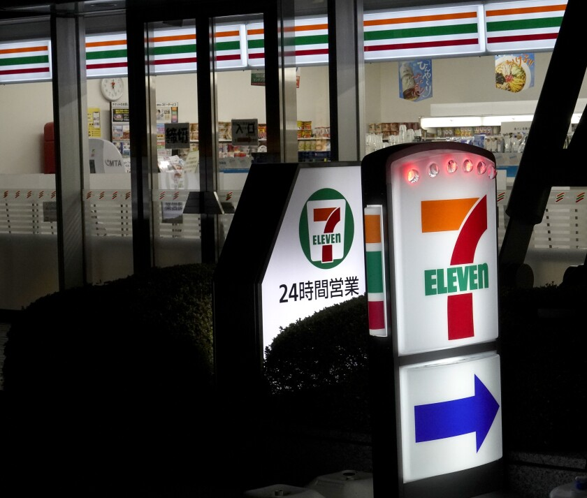 A 7-Eleven store sign at night in Tokyo.
