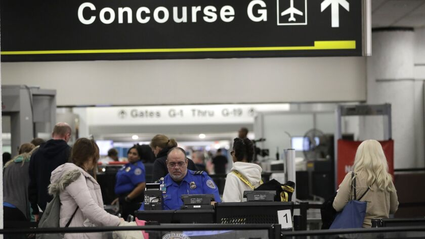 A Transportation Security Administration official works the entrance to Concourse G at Miami International Airport. The terminal is being closed this weekend as the federal government shutdown stretches toward a fourth week.