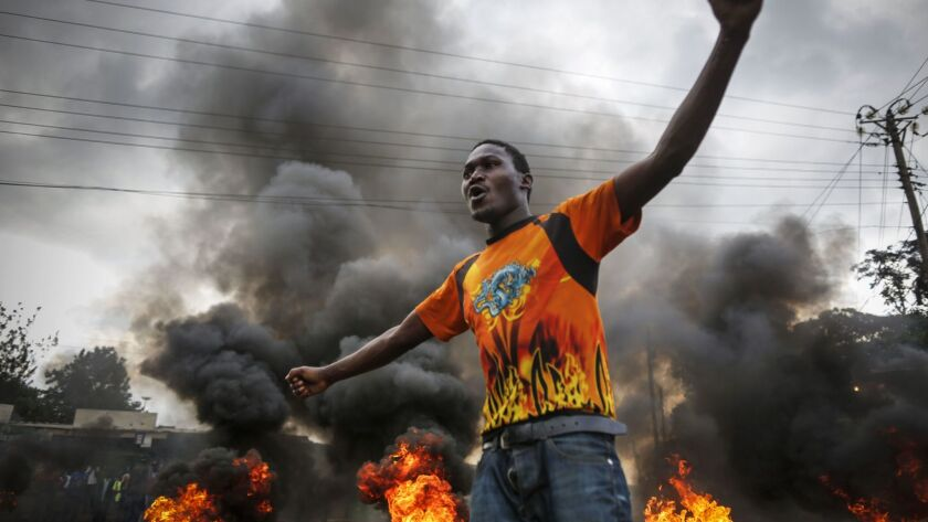 A supporter of presidential candidate Raila Odinga reacts in front of a burning barricade set up to block vehicles from delivering electoral materials to the polling stations in their areas in Kibera slum, one of the opposition strongholds in Nairobi, Kenya, on Oct. 25, 2017.