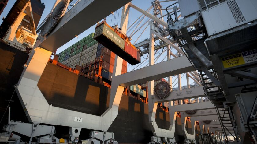 FILE- In this Jan. 30, 2018, file photo, a ship to shore crane loads two shipping containers togethe