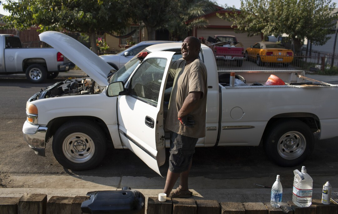 New resident Gailton Moore spends his time refurbishing a pickup truck in front of his home in Stratford.