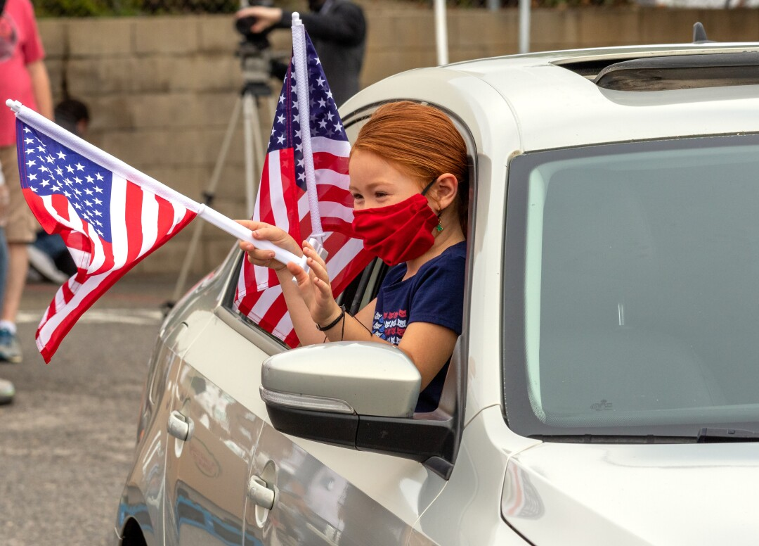 Isabel Hooper, 5, waves to volunteers after receiving a truck full of food while taking part in a rolling caravan for veterans and active duty at the Oceanside Municipal Airport on Monday. The event put on by the Power of One Foundation and the Patriot's Voice Foundation gave each vehicle a window clip American Flag before they rolled past multiple food stations to receive the food.