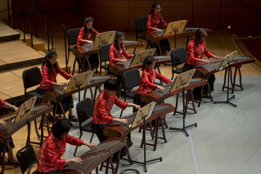 A group of student musicians perform on the Guzheng