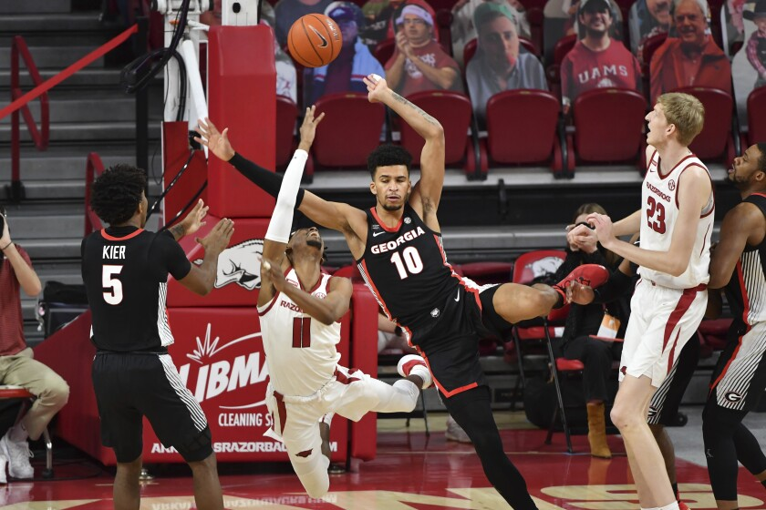 Arkansas guard Jalen Tate (11) is fouled by Georgia defender Toumani Camara (10) during the first half of an NCAA college basketball game, Saturday, Jan. 9, 2021, in Fayetteville, Ark. (AP Photo/Michael Woods)