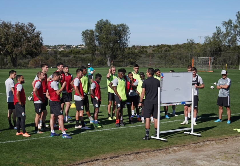 San Diego Loyal soccer team assistant coach Nate Miller talks to the team during a practice at the Chula Vista Elite Athlete Training Center on Jan. 28.  Coach Landon Donovan, right, looks on.