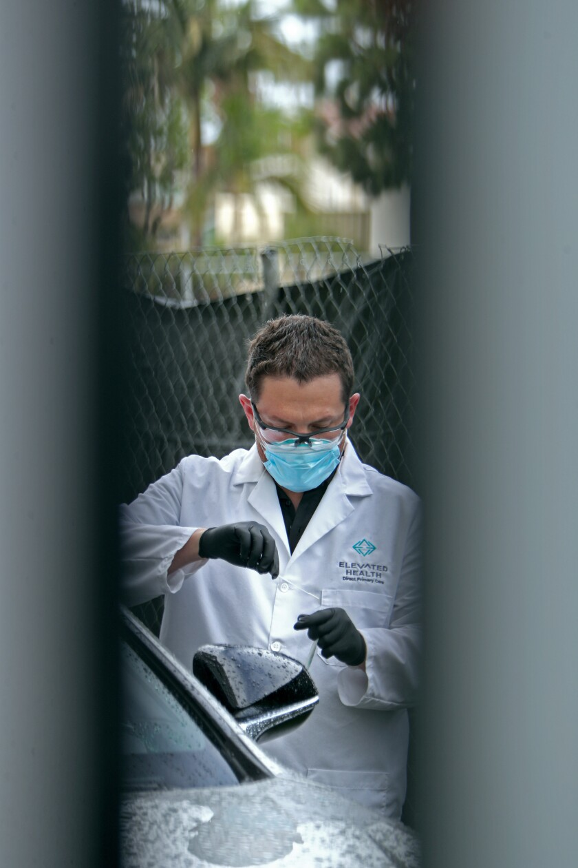 Dr. Matthew Abinante is seen through a doorway putting away a drive-up sample for a novel coronavirus test he performed on a patient outside his office in Huntington Beach on Thursday.