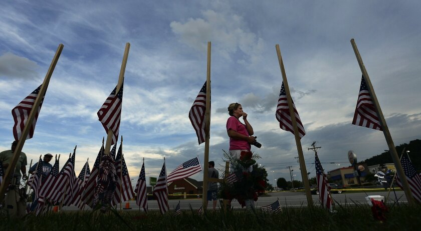 A woman walks past a makeshift memorial with five U.S. flags at the Armed Forces Career Center in Chattanooga, Tenn., on July 21. The memorial honors four Marines and one Navy petty officer killed in a shooting rampage.