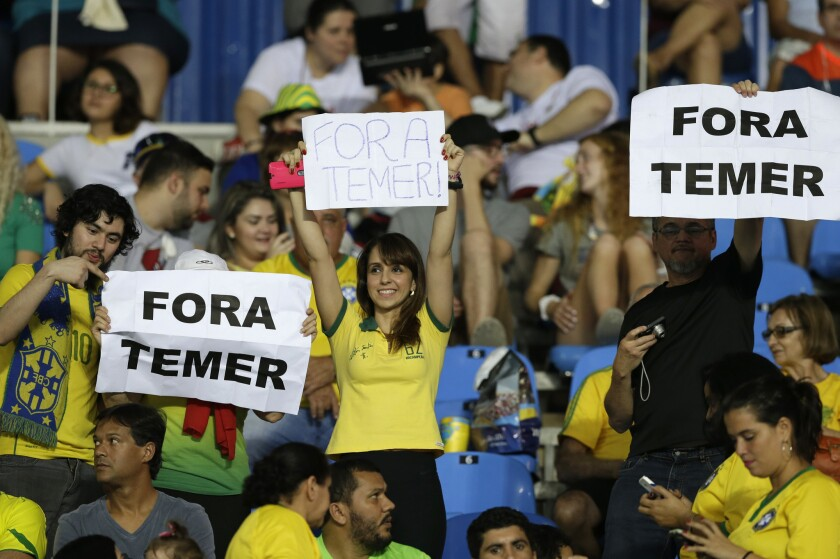 """In this Aug. 6, 2016 photo, fans hold signs that read in Portuguese; """"Temer Out"""" prior to a group E match of the women's Olympic football tournament between Brazil and Sweden at the Rio Olympic Stadium in Rio de Janeiro, Brazil. A court ruling banning the removal of protesters from Olympic venues is fueling debate on whether Brazil's political crisis should be kept out of the athletic competition. The ruling Monday came after a Brazilian Olympic volunteer defaced his official credentials to demonstrate his opposition to orders to escort out of stadiums fans holding up signs against interim President Michel Temer. (AP Photo/Leo Correa)"""