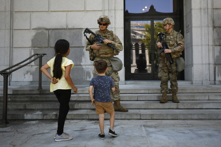 Bianca Luna, 6, left, and Elijah Ducey, 3, ask members of the California National Guard if they would like some water, as they stand guard at the Stanley Mosk Library and Courts Building in Sacramento, Calif., Tuesday, June 2, 2020. More than 2,400 members are deployed in several cities to guard infrastructure, freeing up law enforcement officers to respond to incidents like vandalism and looting that occurred during demonstrations sparked by the death of George Floyd, who died after being restrained by Minneapolis police officers on May 25. (AP Photo/Rich Pedroncelli)