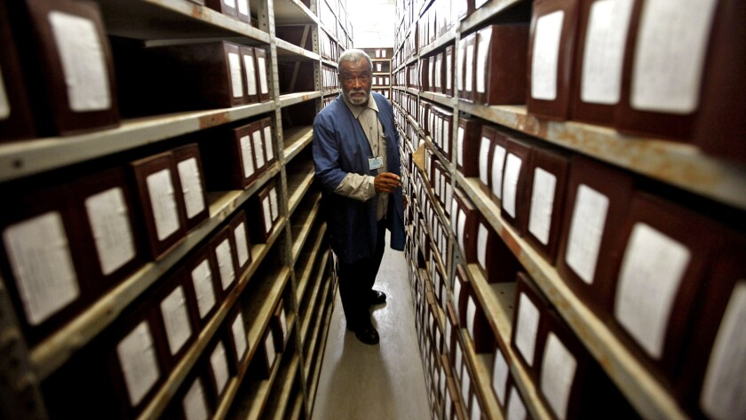 Cemetery caretaker Albert Gaskin stands in a room where hundreds of boxes are stored, each containing the ashes of a person who has been cremated by L.A. County.