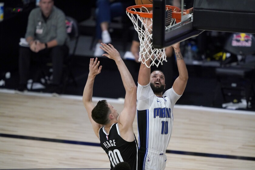 Evan Fournier del Magic de Orlando lanza el balón sobre Rodions Kurucs de los Nets de Brooklyn en el partido del viernes 31 de julio del 2020 en Lake Buena Vista, Florida. (AP Photo/Ashley Landis, Pool)