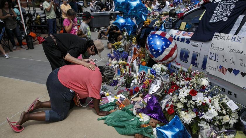 Djuana Franklin es consolada por un residente del área. Ella llora en el memorial en honor a las víctimas en Dallas.