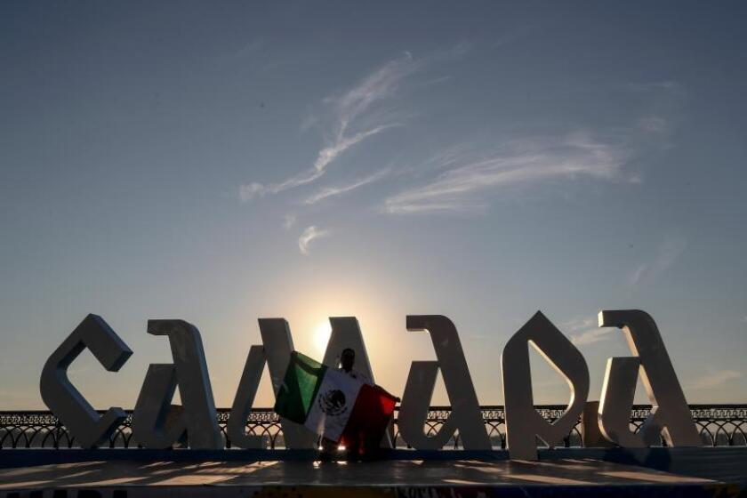 A supporter holds up the Mexican flag in front of a sign that reads 'Samara' on the banks of the Volga river in Samara, Russia. EFE