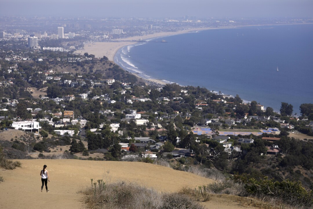 A hiker walks along the Los Lioness Trail, overlooking the ocean