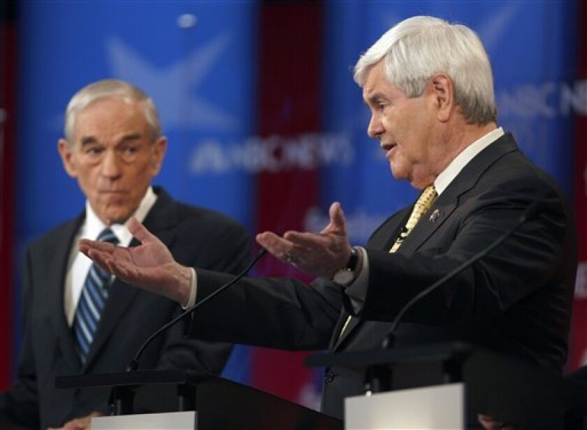 """FILE - In this Jan. 8, 2012 file photo, Republican presidential candidates, former House Speaker Newt Gingrich, right, andRep. Ron Paul, R-Texas participate in the Republican presidential candidate debate in Concord, N.H. _ The ghosts of the Vietnam War are rearing their heads as GOP presidential candidates fight for position in the primary elections. Vietnam veteran Paul has called Gingrich a """"chicken hawk,"""" asserting in Saturday's GOP candidate debate that Gingrich shirked military service himself and so shouldn't have the power to send others to war. Gingrich answered that he simply """"wasn't eligible"""" to go. (AP Photo/Charles Krupa, File)"""